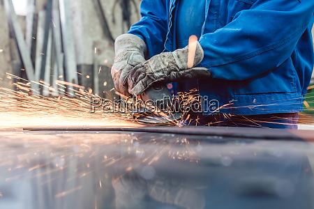 worker in metal factory grinding workpiece
