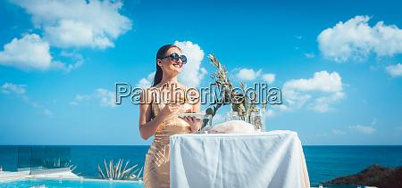 woman in golden dress having food