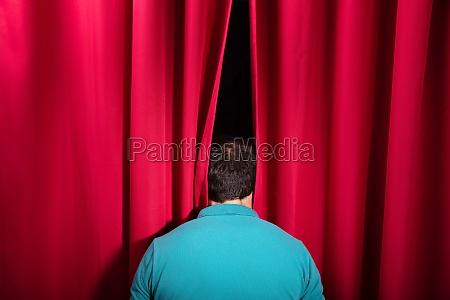 mann pumah sich durch einen buehnenvorhang