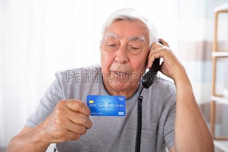 mann mit kreditkarte mit landline telefon