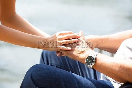frau haelt hand ihres vaters
