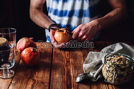 mann oeffnet granatapfel mit einem messer