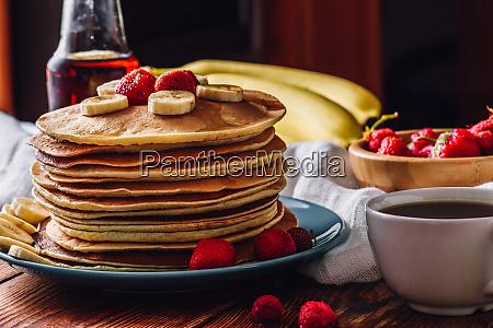 pfannkuchen mit teetasse und fruechten