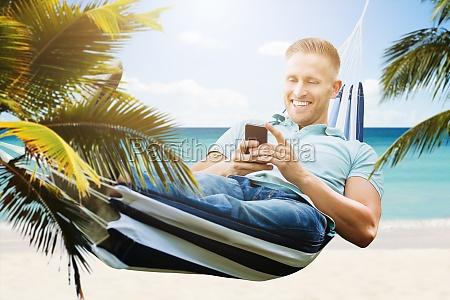 happy man using smartphone in hammock