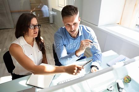 zwei geschaeftsleute schauen sich computer mit