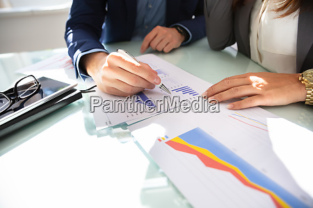 businesspeoples hand analyzing graph in office
