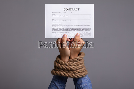 womans hand tied with rope holding