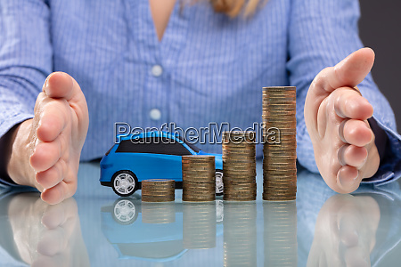 businesswoman protecting stacked coins and blue