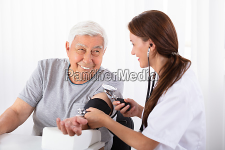 doctor checking blood pressure of male