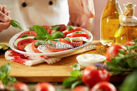 chef adding fresh basil to a