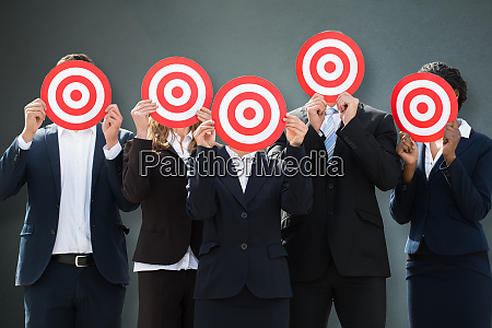 group of businesspeople hiding their faces