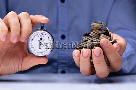 person holding stopwatch and golden coins