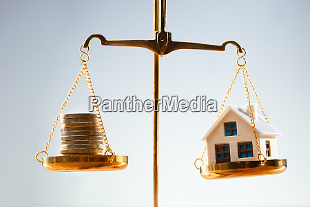 stacked coins and house model balancing