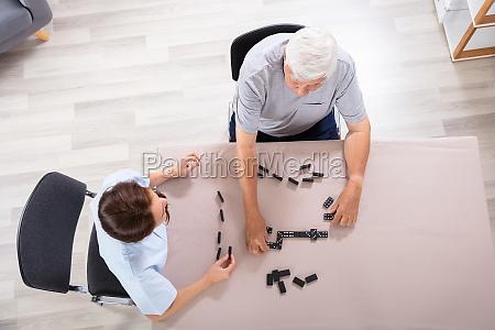 caretaker and senior man playing dominoes