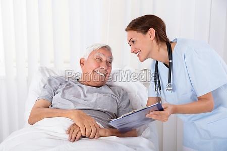 krankenschwester mit clipboard besucht senioren patienten