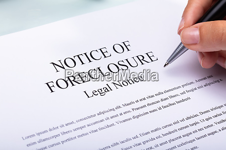woman holding pen over notice of