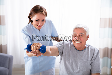 nurse helping senior man with dumbbell