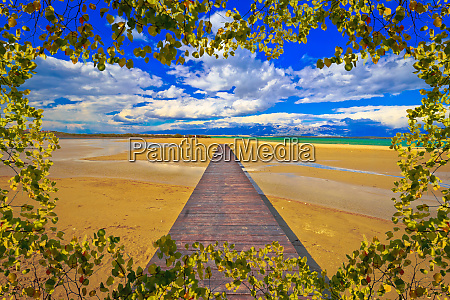 wooden boardwalk and sand beach of