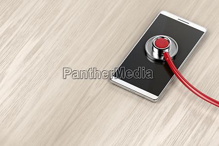 smartphone und sthetoskop auf holztisch