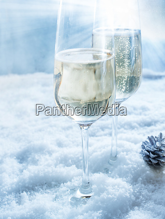 two champagne glasses in snow