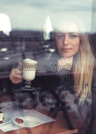 vertraeumtes maedchen mit latte im cafe