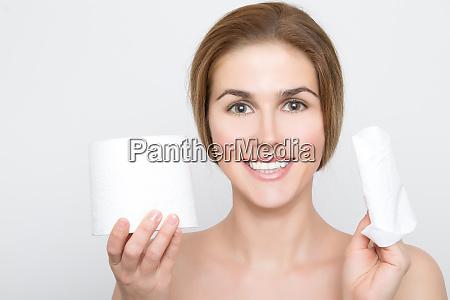 frau haelt ein stueck toilettenpapier und