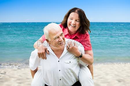 happy senior man giving piggyback to
