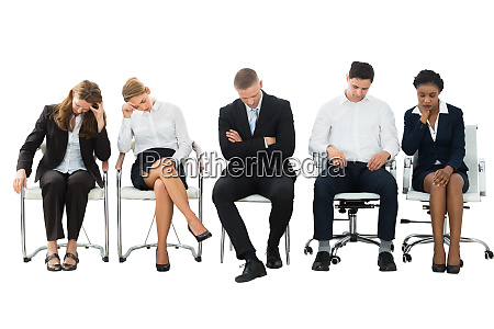 group of businesspeople sleeping on chair