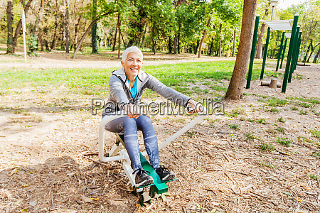 elderly woman exercising at outdoor fitness