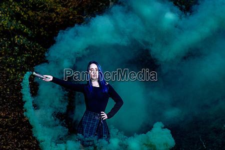 attraktives maedchen mit gruenem dunklem rauch
