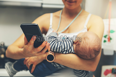 mother is using smartphone while holding