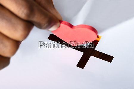 man inserting heart shape in crucifix