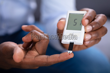 man checking blood sugar level with