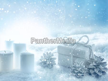 kerzen und ein geschenk im verschneiten