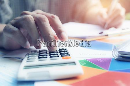 mann mit taschenrechner mit aktienfinanzindizes mit