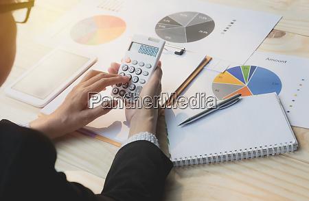 geschaeftsfrau mit taschenrechner mit aktienfinanzindizes mit