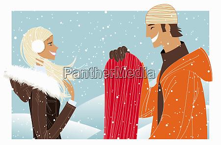 paar lacht im schnee mit snowboard