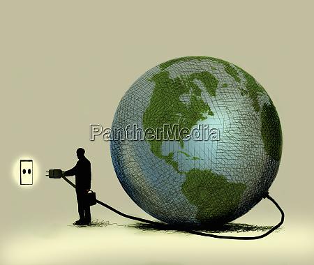 mann verbindet globus mit wandsteckdose