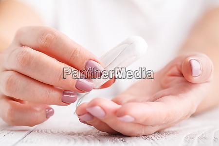 frau haelt menstruationstampon auf rosa hintergrund