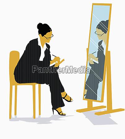 geschaeftsfrau schaut in spiegel