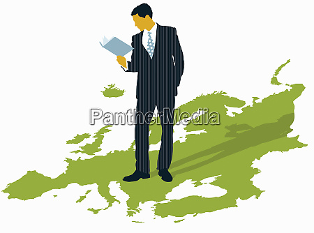 businessman reading book standing on map