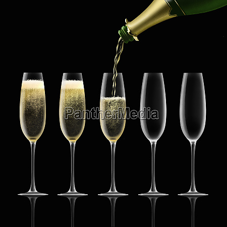 champagne bottle pouring into flutes on