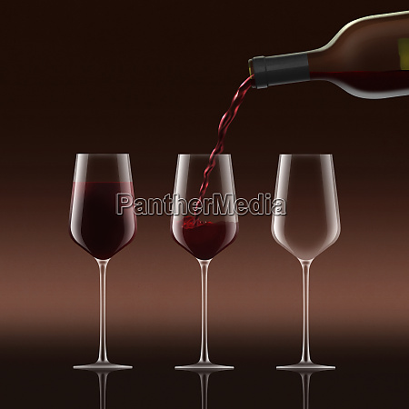 red wine being poured into three
