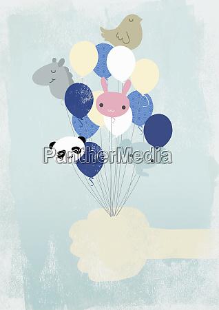 hand holding animal shaped helium balloons