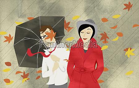 wind blowing autumn leaves around man
