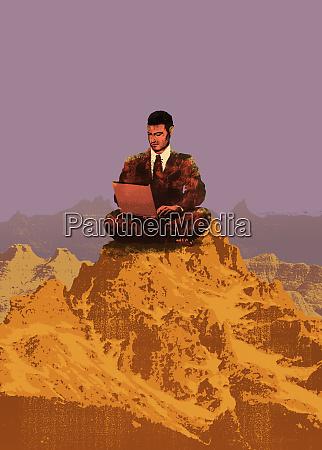 businessman using laptop on mountain
