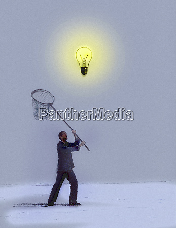 businessman chasing hovering light bulb with