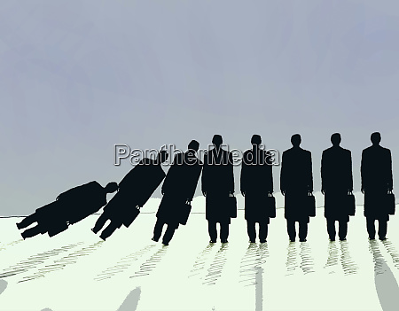 row of businessmen falling in domino