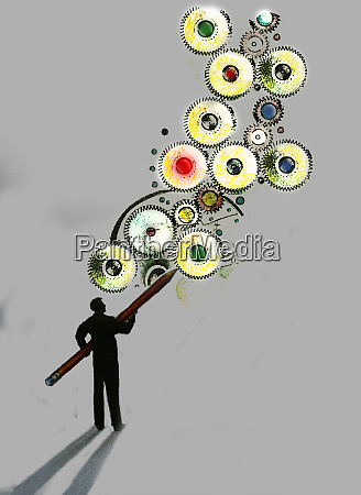 man drawing connected cogs with large