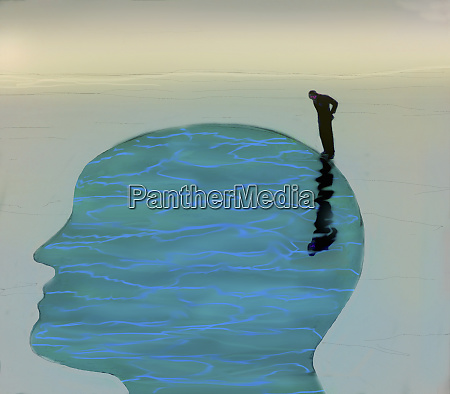 man looking down into tranquil water